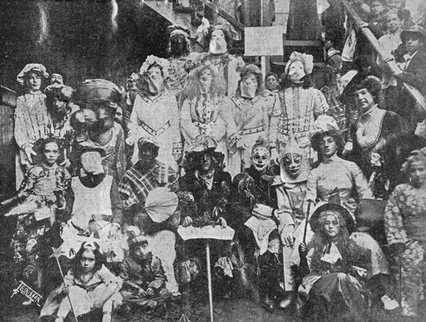 A group of masked and costumed Mardi Gras revelers on Frenchman Street, New-Orleans, circa 1910